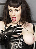 Corseted dominatrix in dungeon high heels whip