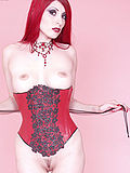 Redhead strips off corset and fetish hobble skirt