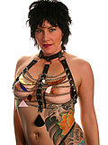 Tattooed busty milf in chain and leather harness