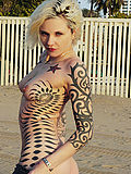 tattooed blonde gets naked at the beach